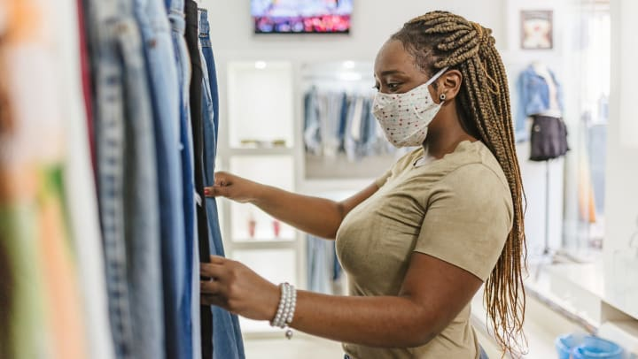 Woman shopping for clothes in boutique shop.