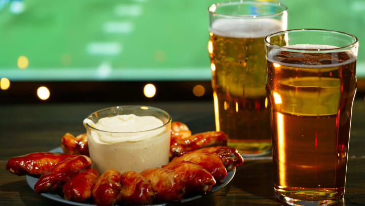 Barbecue wings and two glasses of beer in the foreground with football playing on a TV in the background.