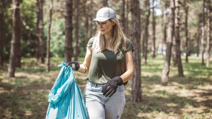 A Woman collecting garbage from a neighborhood park