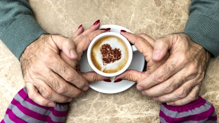 Older man and woman holding hands over a cup of coffee with a heart on it.