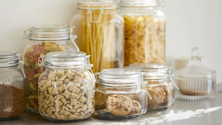 Close-up of various pantry ingredients in airtight glass containers.