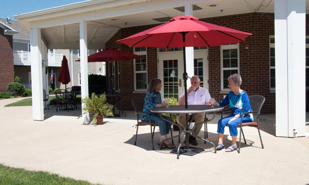 Residents sitting in covered outdoor seating at The Keystones of Cedar Rapids in Cedar Rapids, Iowa