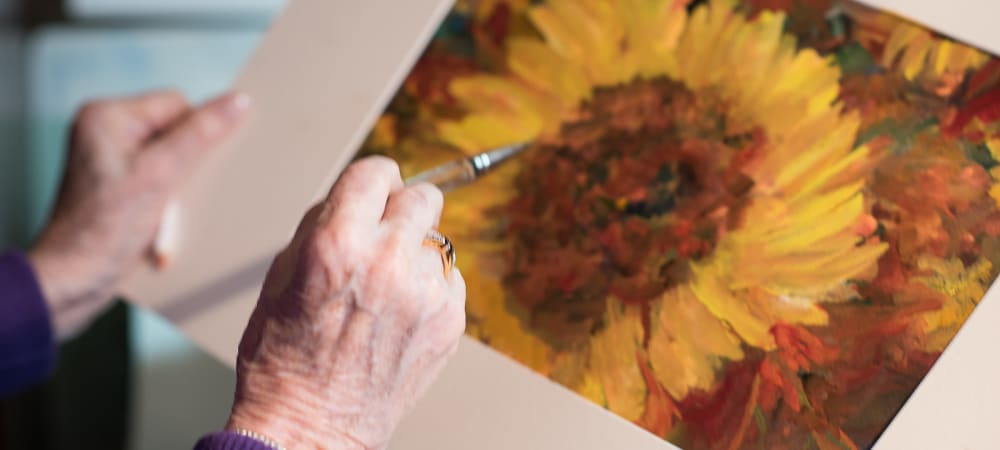 Resident painting picture of sunflower at The Springs at Tanasbourne in Hillsboro, Oregon