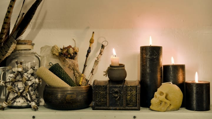 Halloween decor with black candles, a wooden box, and skull