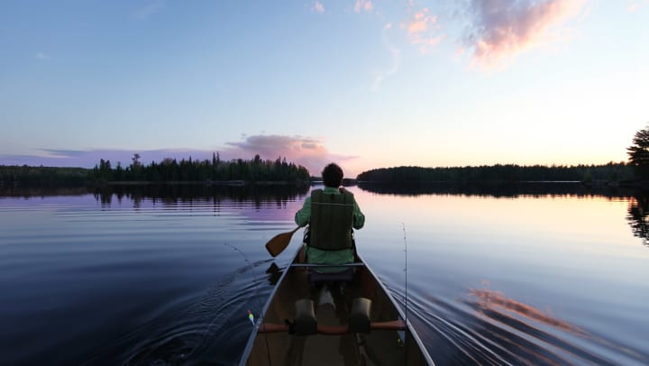 A man sitting in a canoe on the water during sunset with a paddle in his hand.