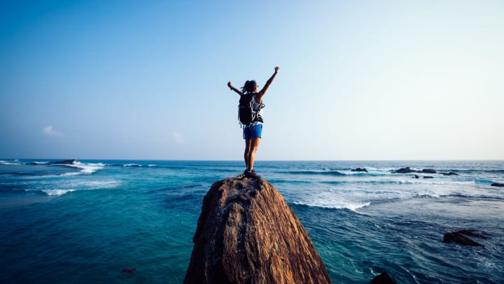 A woman standing on a rock at the edge of the ocean with her arms raised in the air.