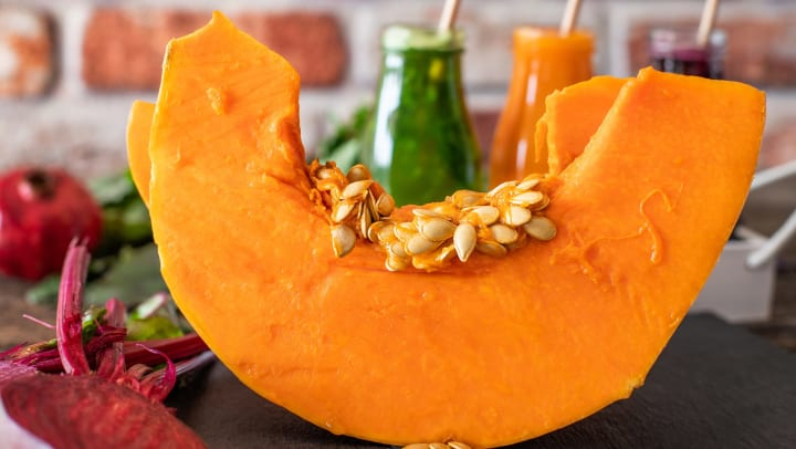 Slice of pumpkin with some seeds, and pumpkin concoctions behind it at Olympus Team Ranch