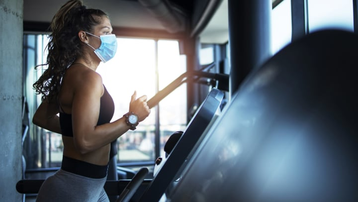 A woman in athletic wear and a medical mask runs on a treadmill.
