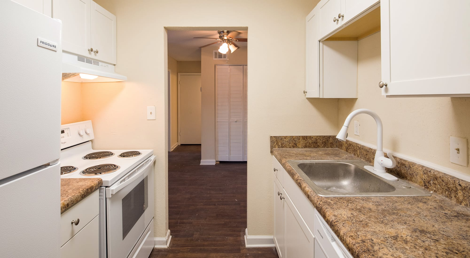Spacious kitchen with white cabinets and white appliances at Premier Apartments in Austell, Georgia