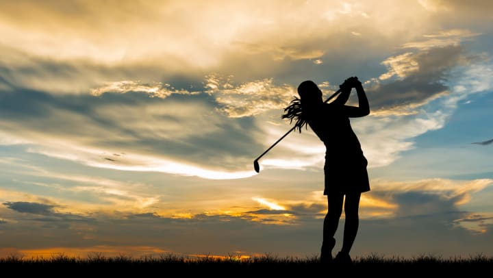 The silhouette of a female golfer at the end of her swing.