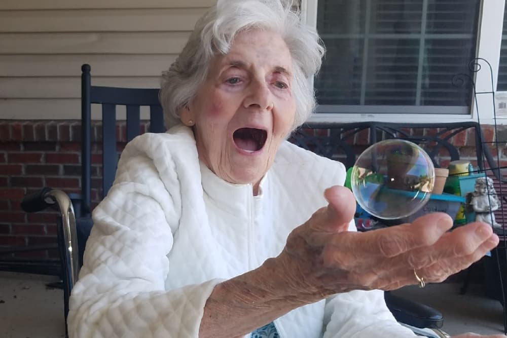 A resident playing with bubbles at Aspen Place Health Campus in Greensburg, Indiana