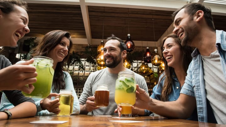 A smiling group of friends holding drinks in mason jars at a bar