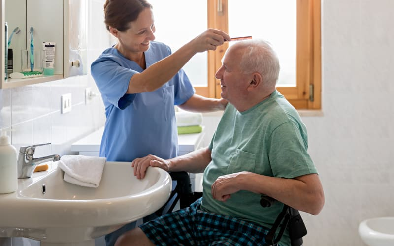 Caregiver combing a resident's hair at Northglenn Heights Assisted Living in Northglenn, Colorado