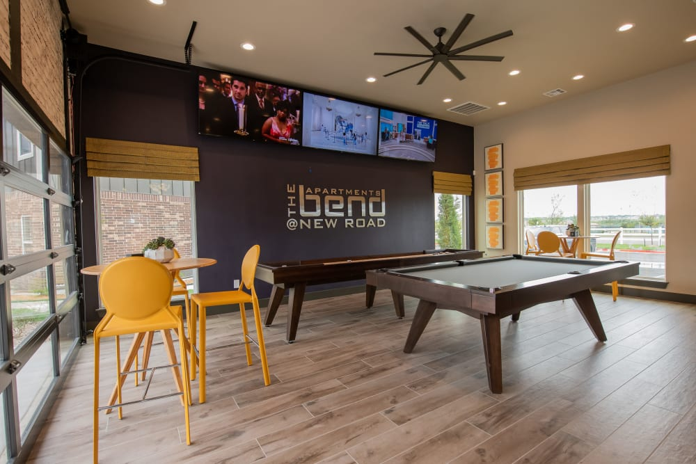 Community shuffle board and billiards table in Bend at New Road Apartments's clubhouse in Waco, Texas