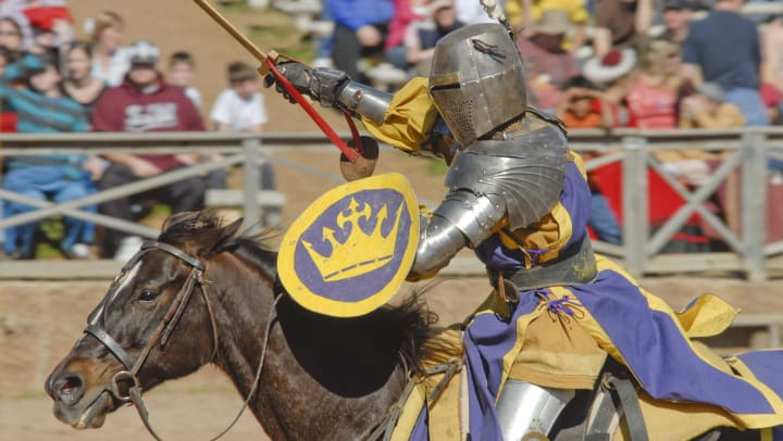 A knight in full armor jousts on horseback with a crowd watching in the background.
