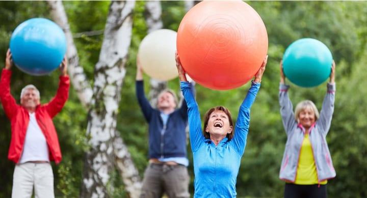 Seniors with exercise balls outside