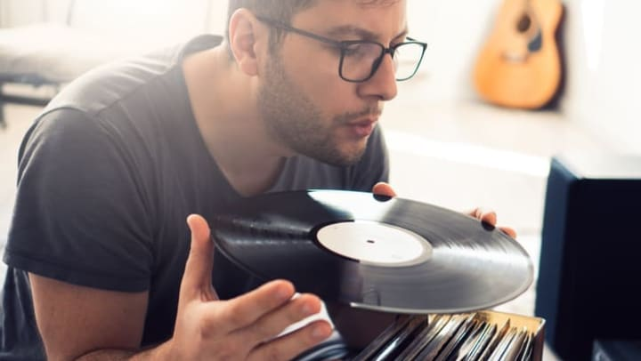 Man taking a record out of his record collection and getting ready to play it at {{location_name}}.