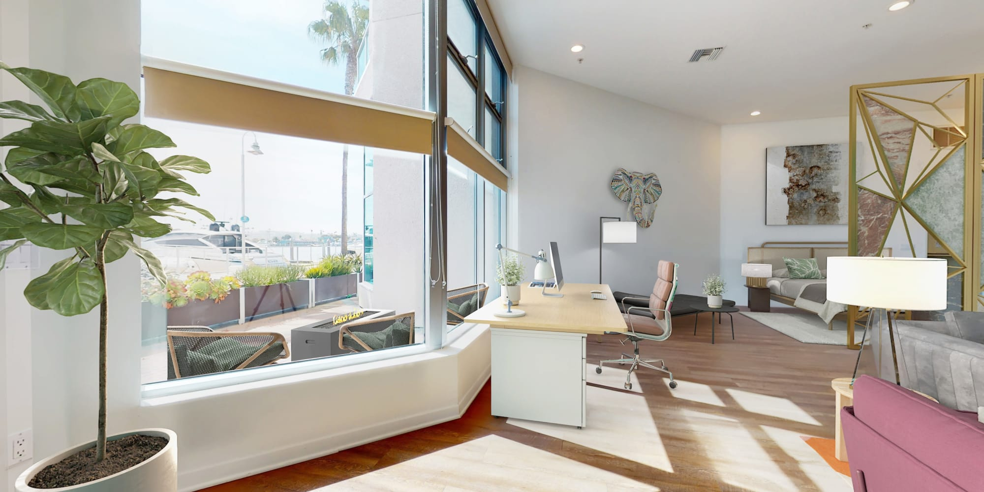 Spacious loft apartment's work space with large windows, waterfront view of the marina, and hardwood floors at Esprit Marina del Rey in Marina Del Rey, California