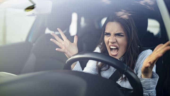 Woman in a car holding hands up and making an angry face.