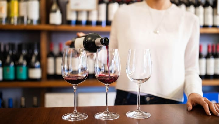 Woman in a long-sleeve white shirt pouring red wine into one of three wine glasses on the counter inside a wine bar