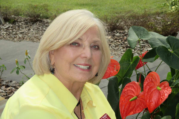 Resident in front of beautiful flora at Ashton Gardens Gracious Retirement Living in Portland, Maine
