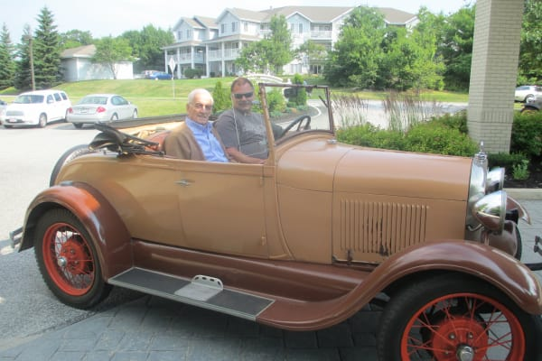 Two gentlemen from Camden Springs Gracious Retirement Living in Elk Grove, California, in a classic car