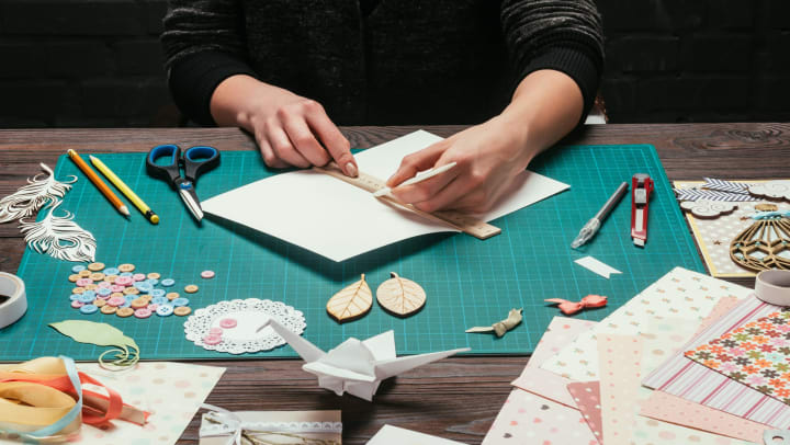 Woman sitting at a table and working on paper crafts.