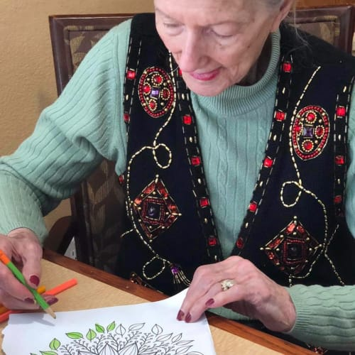 A smiling resident coloring a picture at Oxford Glen Memory Care at Sachse in Sachse, Texas