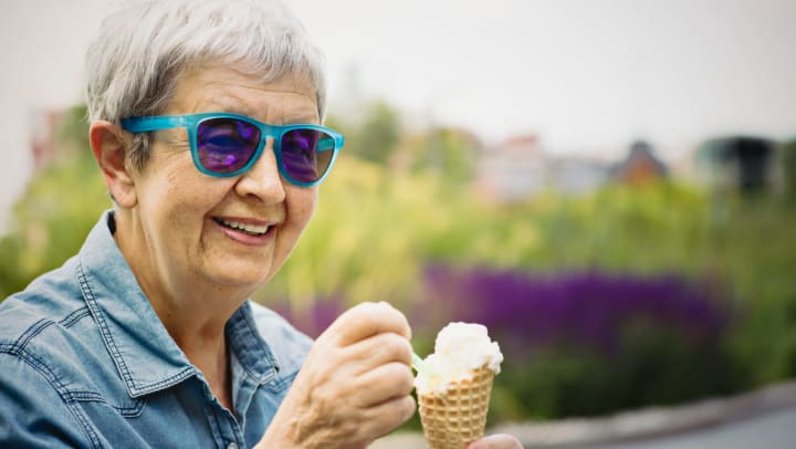Senior woman wearing colored glasses smiling, eating an ice cream cone