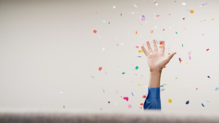 A person's hand throwing confetti in the air