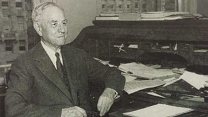 R.D Merrill sits at desk