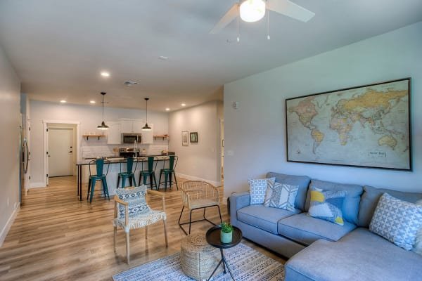 Living area with hardwood floors and ceiling fan in open-concept floor plan of model home at District Lofts in Gilbert, Arizona