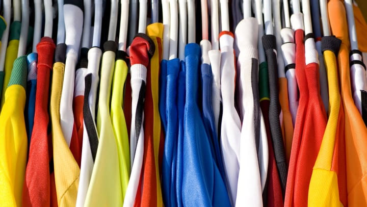 A series of colorful sports jerseys on white clothing hangers