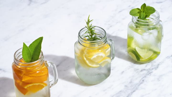 Three Mason jars on a marble countertop filled with citrus fruits and herbs.