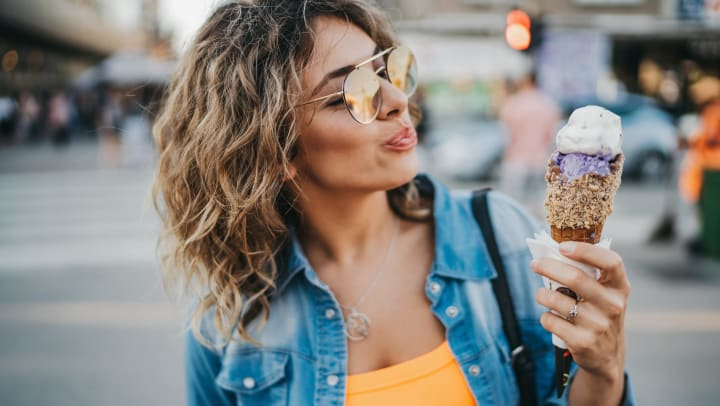 A happy woman eating ice cream in the city on a sunny summer day.