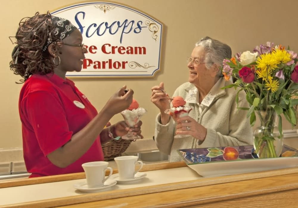 A resident and staff member enjoying ice cream together at Patriots Glen in Bellevue, Washington.