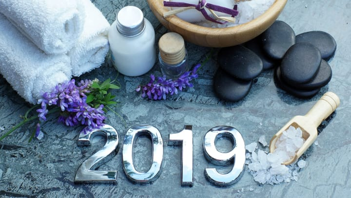 A collection of spa-related items, including stones, salt, and towels, and the year 2019.