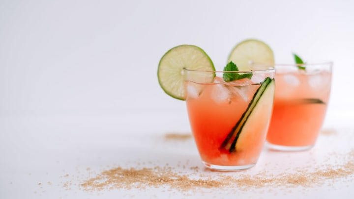 Grapefruit margarita with lime, mint, and ice against a white background.