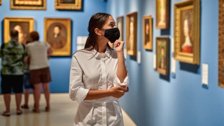 Woman in an art museum with bright blue walls, looking at a painting with her hand to her chin.