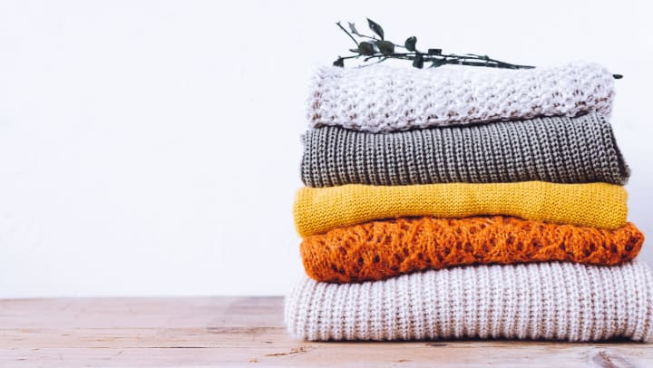 Stack of sweaters a resident just received from an online subscription service at The Enclave in Brunswick, Georgia