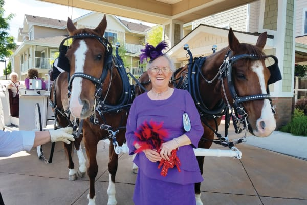 Resident posing in front of a horse-drawn carriage at Ashton Gardens Gracious Retirement Living in Portland, Maine