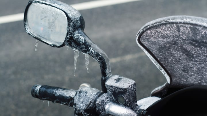 Closeup of frozen motorcycle windshield and rear mirror.