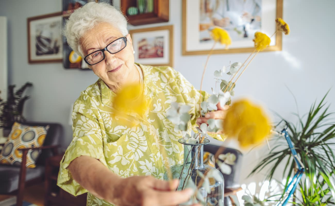 A resident putting flowers in a vase at The Oaks, A Merrill Gardens Community in Gilbert, Arizona.