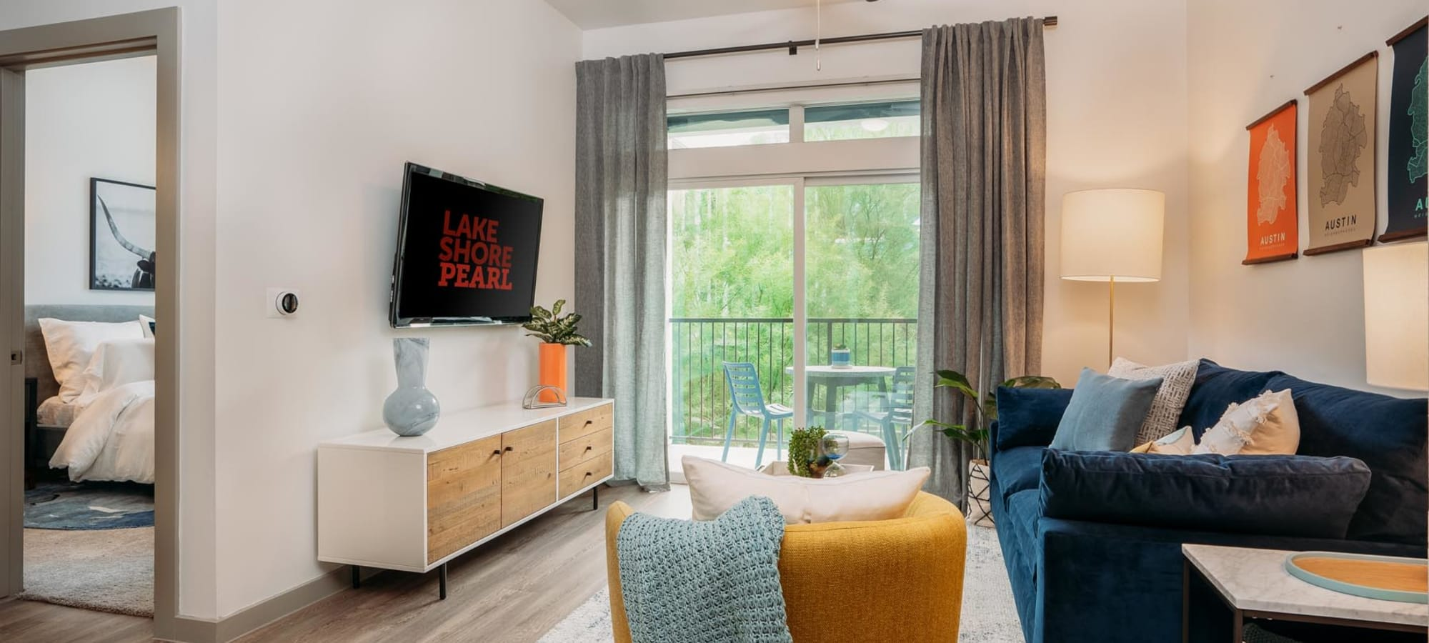 Model home's well-furnished living area with a wooded view outside Lakeshore Pearl in Austin, Texas