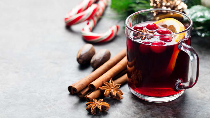 Mulled red wine with orange slice and cranberries surrounded by cinnamon stocks and candy canes