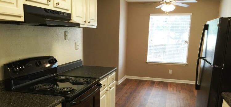 Ceiling fan, hardwood floors, and sleek black appliances in kitchen at Abbots Glen in Norcross