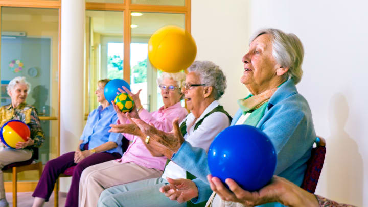 Residents sitting in chairs throwing a ball into the air