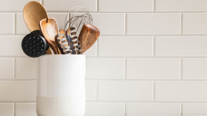 A stylish white subway tile backsplash with kitchen utensils in a ceramic jar on a granite countertop.