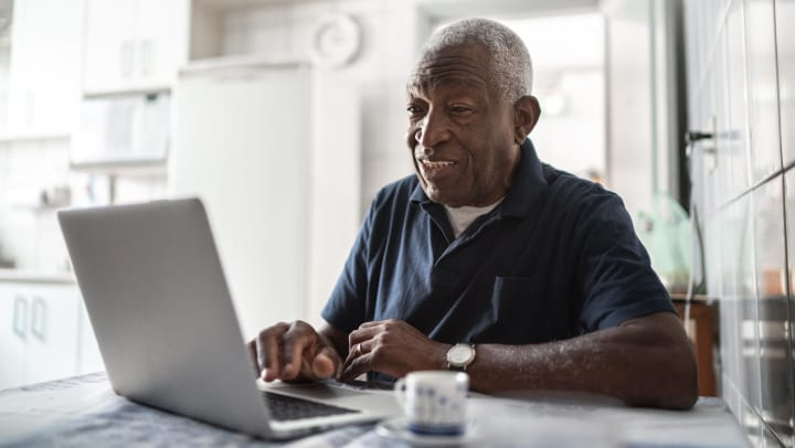 Elderly man looking at a laptop and smiling.