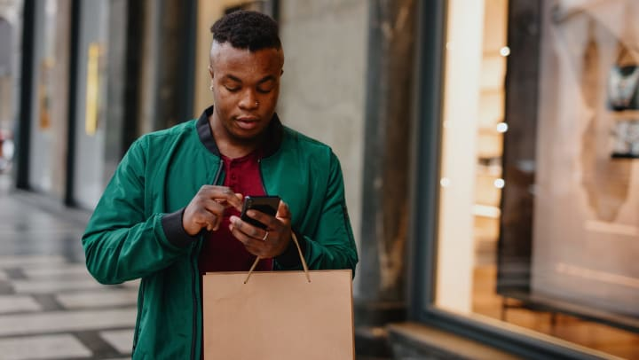 A young man using smartphone while holding shopping bags.